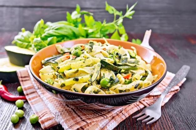 Tagliatelle con zucchine, piselli, fagioli di asparagi, peperoncino e spinaci in un canovaccio da cucina, aglio, forchetta e basilico su tavola di legno scuro