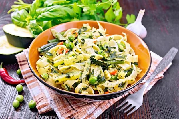 Tagliatelle con zucchine, piselli, fagioli di asparagi, peperoncino e spinaci in un piatto su asciugamano, aglio, forchetta e basilico sullo sfondo di una tavola di legno scuro