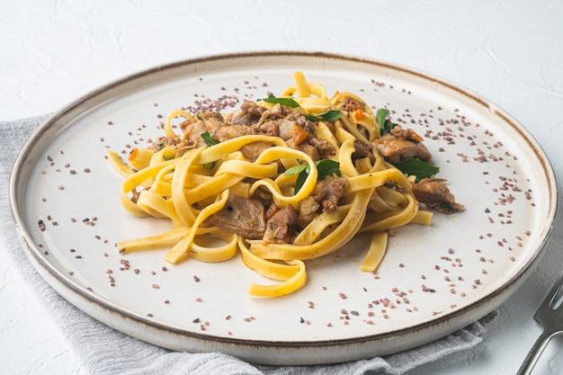 Tagliatelle con finferli e coniglio in umido su piatto, su tavola di pietra bianca