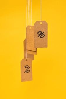 I tag con percentuali disegnate sono appesi a stringhe su uno sfondo giallo, concetto di sconti e vendite