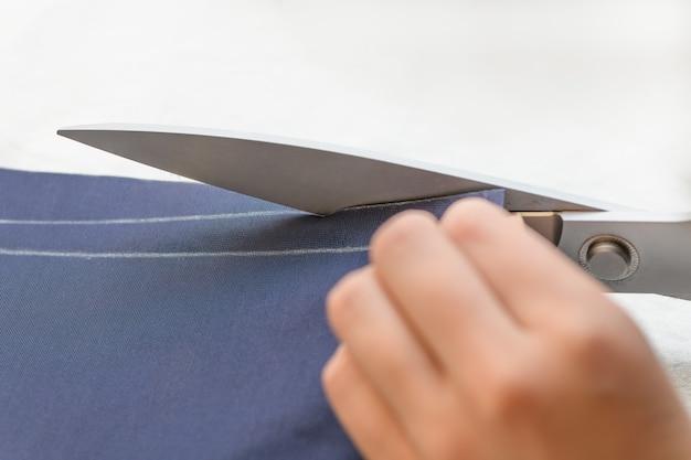 Il sarto taglia il tessuto con le forbici sul tavolo