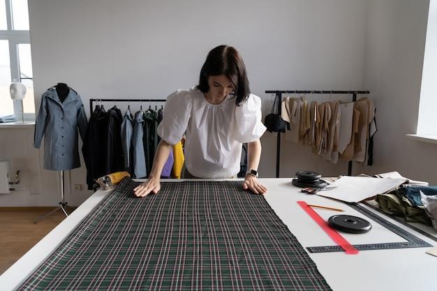 Tessuto su misura su misura in tessuto in studio, giovane designer femminile crea abiti in officina atelier room