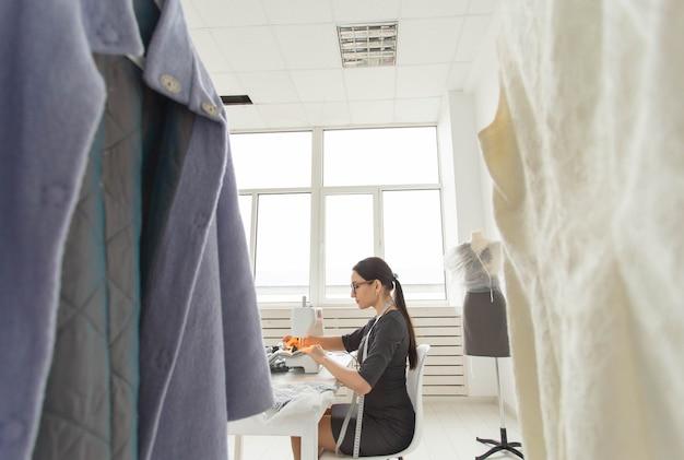 Concetto di sarto, persone e sarta - inquadratura dal basso di attraente giovane donna fashion designer che lavora