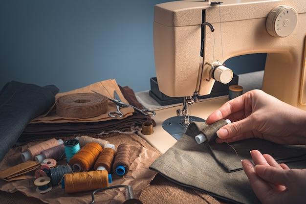 Mani del sarto, filo, tessuto e macchina da cucire su sfondo blu.