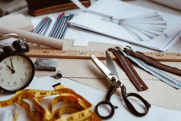 Strumenti del sarto, forbici, metro a nastro e righello sul tavolo da lavoro sartoriale. articoli di design di vestiti