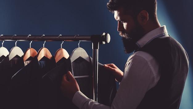 Sarto, sartoria. abito da uomo, sarto nel suo laboratorio. abiti da uomo eleganti appesi in fila. abiti classici da uomo di lusso su rack in un'elegante boutique maschile.