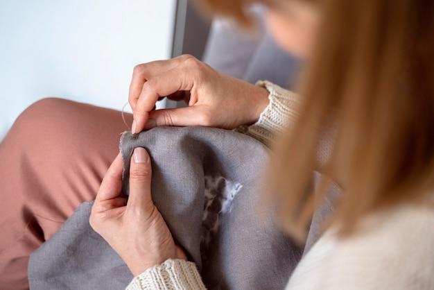 Donna su misura utilizzando strumenti per cucire tessuti