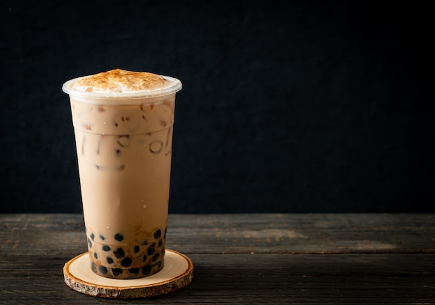 Tè al latte di taiwan con bolle e formaggio bruciato su un tavolo di legno