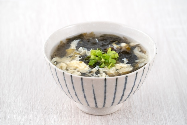 Cibo taiwanese - zuppa di uova di alghe deliziosa fatta in casa in una ciotola su un vassoio da portata su sfondo di tavolo in legno chiaro.