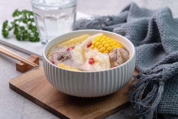 Cibo delizioso zuppa di pollo fatta in casa taiwanese in una ciotola con ananas, zucca amara e mais dolce sul tavolo grigio cemento