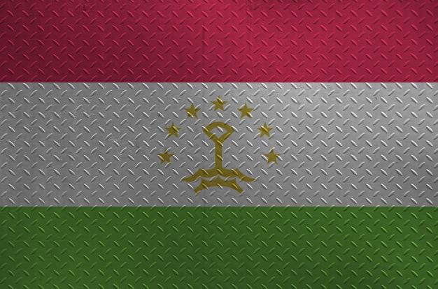 Bandiera del tagikistan raffigurata nei colori della vernice sul vecchio primo piano di piastra metallica spazzolato della parete o. banner con texture su sfondo ruvido