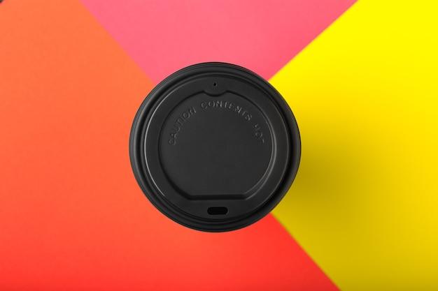 Porta via la tazza di caffè su fondo di carta colorato giallo arancio rosso