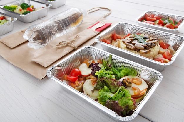 Porta via il cibo in scatole di alluminio. verdure, lattuga e mozzarella con gamberi, sacchetto di carta e bottiglia d'acqua in legno bianco