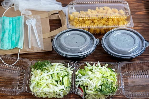Togliere il cibo in contenitori di plastica. insalata e fusilli. consegna del cibo durante la quarantena del coronavirus