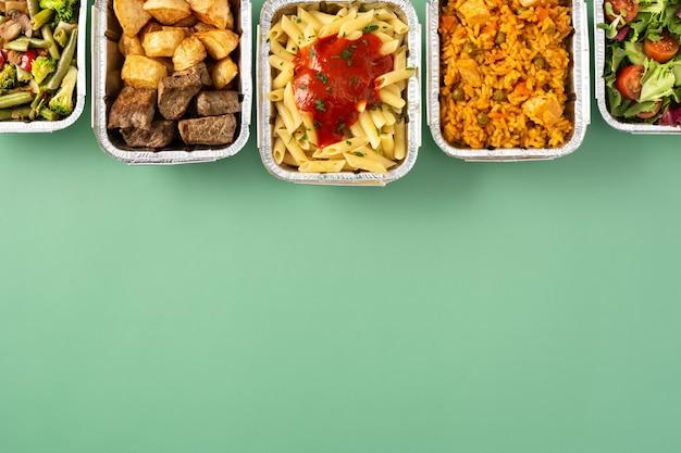 Porta via il cibo sano in scatole di alluminio su sfondo verde