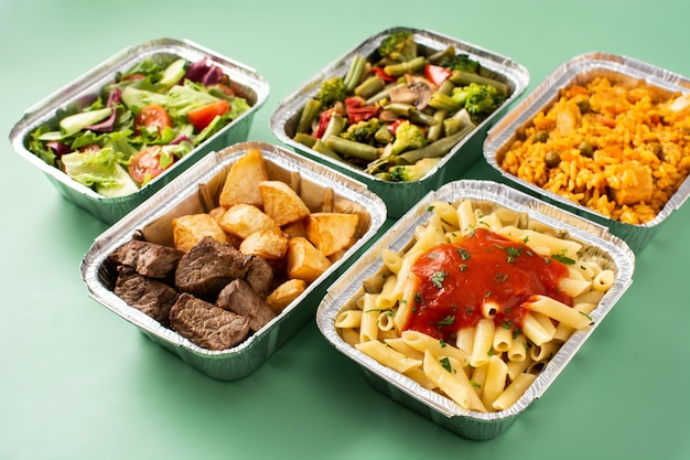 Porta via il cibo sano in scatole di alluminio sul tavolo verde