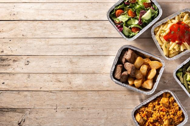Portare via il cibo sano in scatole di alluminio sul tavolo di legno