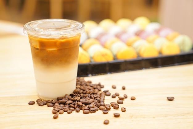 Porta via il latte con il chicco di caffè in giro sul tavolo di legno