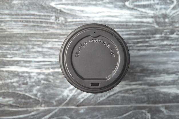 Porta via il cappuccio di plastica della tazza di caffè su fondo di legno grigio