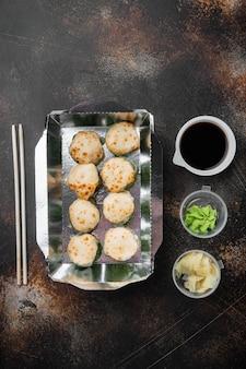 Take away sushi rolls in container, philadelphia rolls e set di involtini di gamberi al forno, su vecchio fondo rustico scuro, vista dall'alto piatta, con copyspace e spazio per il testo