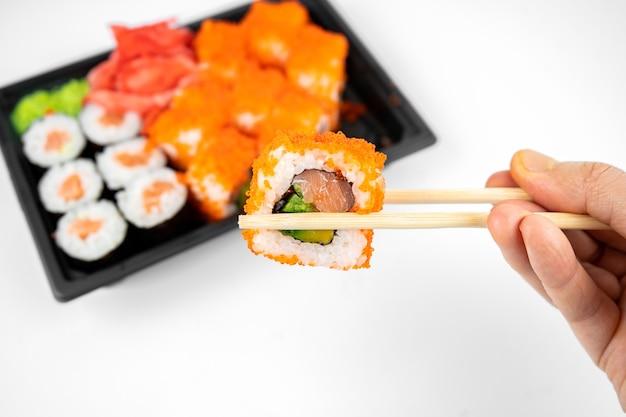 Involtini di sushi da asporto in un contenitore di plastica, california, salmone maki roll, zenzero rosa, wasabi. concetto di consegna di sushi