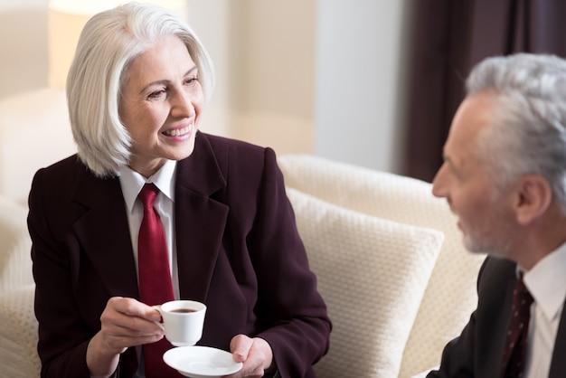 Fare una pausa. allegra imprenditrice invecchiata felice seduta in hotel mentre discute il progetto con il suo collega e beve caffè