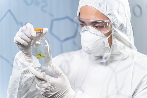 Prendere una decisione. attento ricercatore internazionale che guarda la bottiglia con reagente tossico, concetto di medicina