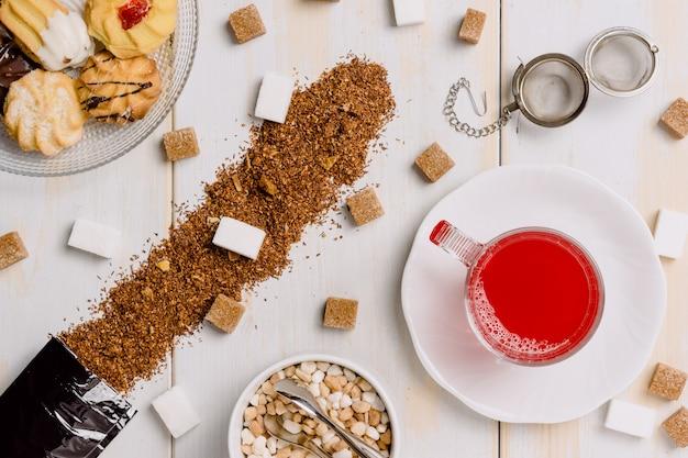 Prendi dall'alto una tazza di tè rosso in vetro trasparente circondata da zollette di zucchero e sparsa sul tavolo con un piatto di pasta nell'angolo sinistro