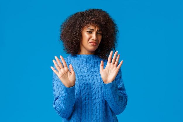Portalo via da me. disgustata e scontenta, sciocca ragazza afro-americana con taglio di capelli afro, stringe la mano in segno di rifiuto, esprime riluttanza e avversione
