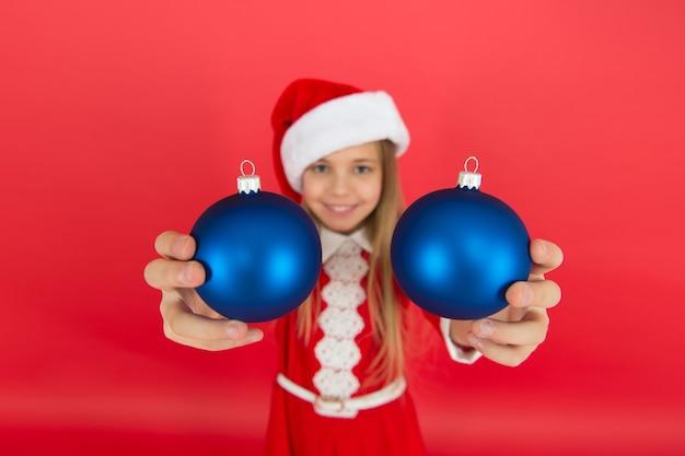 Prendilo. crea decorazioni uniche. decorazione della palla di natale. idee natalizie per decorare la cameretta dei bambini. il costume rosso del bambino felice tiene gli ornamenti di natale da vicino il fuoco selettivo. acquista decorazioni.