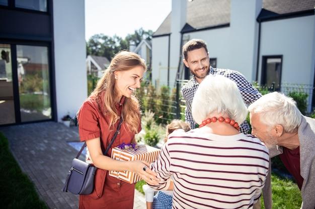 Prendilo. persona di sesso femminile soddisfatta che comunica con i suoi parenti mentre è in piedi nel cortile