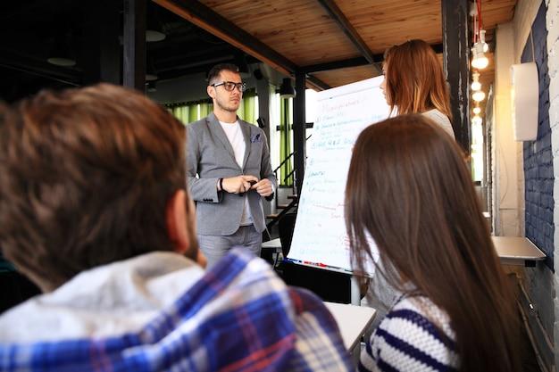 Dai un'occhiata ai nostri risultati! bel giovane con gli occhiali in piedi vicino alla lavagna e indicando il grafico mentre i suoi colleghi ascoltano e si siedono al tavolo