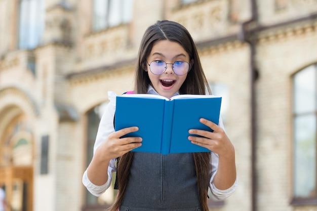 Dai un'occhiata, leggi un libro. il bambino felice ha letto il libro all'aperto. biblioteca scolastica. educazione all'alfabetizzazione. lista di lettura. imparare a leggere. lettura casalinga. lezione di letteratura. corsi di lingua straniera.