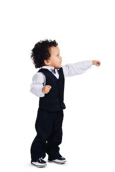 Prendimi la mano! vista laterale del piccolo bambino africano che allunga la mano e guarda lontano mentre sta in piedi su sfondo bianco