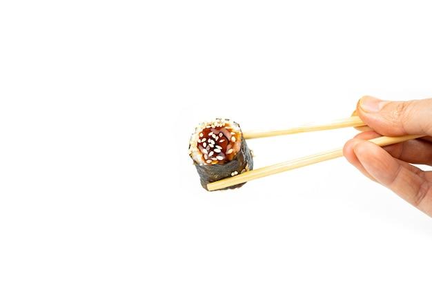 Prendi un unagi maki roll con bacchette di bambù su sfondo bianco, cibo asiatico, cucina giapponese