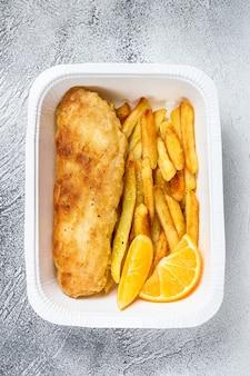 Scatola da asporto piatto di pesce e patatine fritte con patatine fritte. sfondo bianco. vista dall'alto.