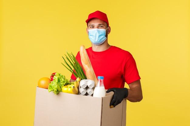 Consegna da asporto covid quarantena e concetto di generi alimentari corriere allegro in maschera medica e un...