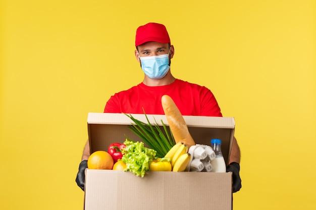 Consegna da asporto covid quarantena e concetto di spesa allegro corriere sorridente in uniforme rossa e...