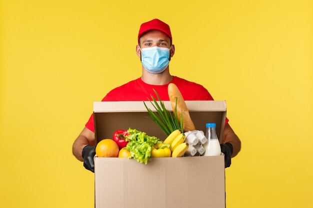 Consegna da asporto covid quarantena e concetto di generi alimentari corriere sorridente felice in uniforme rossa e me...