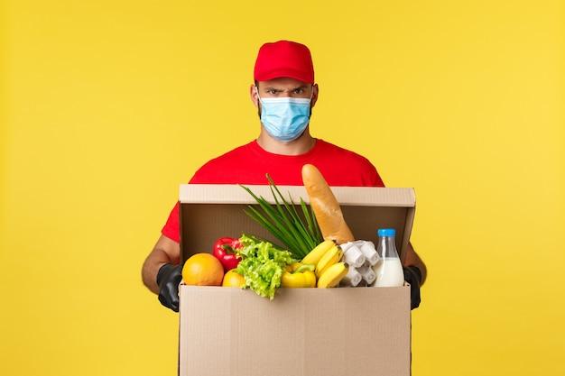 Consegna da asporto covid quarantena e concetto di generi alimentari corriere scontroso serio in maschera medica e ...