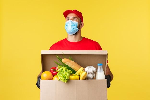 Consegna da asporto covid quarantena e concetto di generi alimentari giovane corriere in berretto rosso e maglietta uniforme...