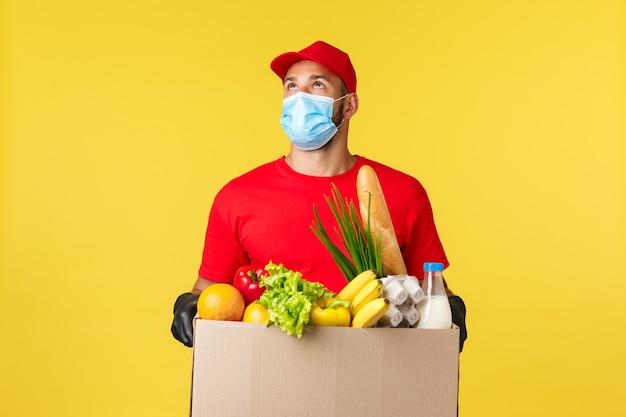 Consegna da asporto cibo e bevande covid quarantena e concetto di generi alimentari corriere guardando costruire...