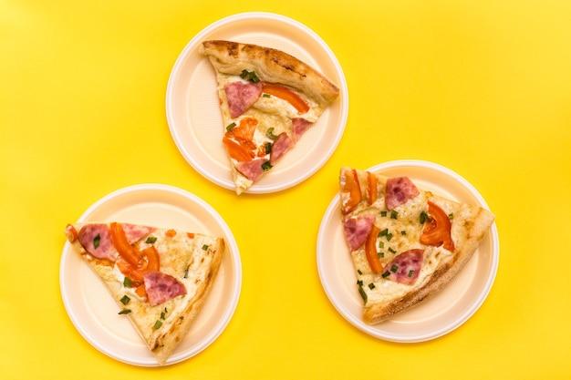 Da asporto e consegna. tre pezzi di pizza in piatti di plastica usa e getta su uno sfondo giallo. pranzo per un gruppo di amici