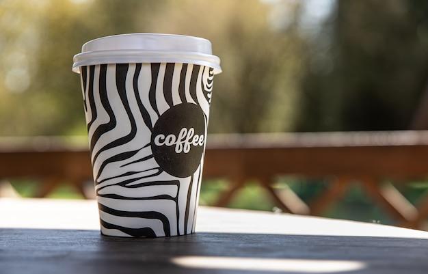 Tazza usa e getta da asporto con caffè su panca di legno nel giardino mattutino