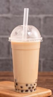 Da asporto con elemento usa e getta concetto popolare taiwan bevanda bolla tè al latte con bicchiere di plastica e paglia sul tavolo in legno sfondo, vicino, spazio di copia