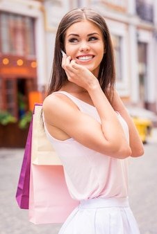 Prendendo sulle vendite. bella giovane donna sorridente che tiene in mano le borse della spesa e parla al telefono cellulare mentre si trova all'aperto e si guarda alle spalle