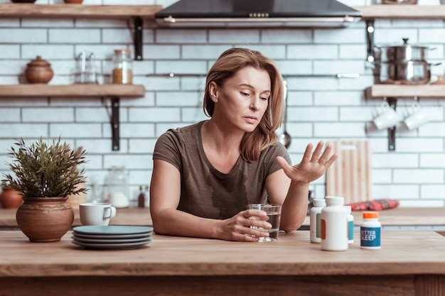 Assunzione di antidepressivi. donna depressa dai capelli biondi che prende antidepressivi dopo la depressione e le lotte familiari