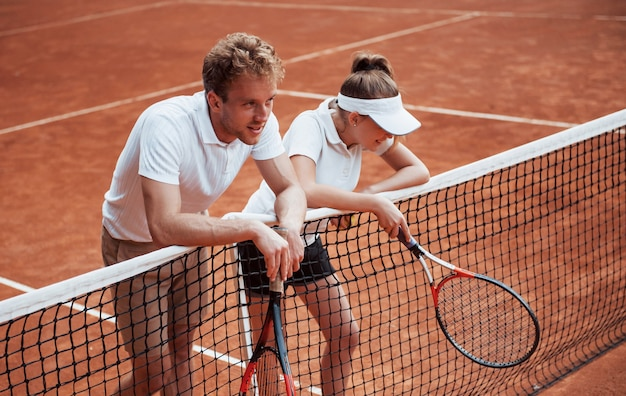 Fare una pausa appoggiandosi alla rete. due persone in divisa sportiva giocano a tennis insieme sul campo.