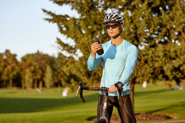 Prendersi una pausa giovane uomo atletico in abbigliamento sportivo e casco protettivo in piedi con la sua bici