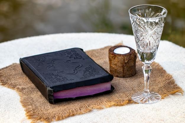 Fare la comunione. tazza di vetro con vino rosso, pane e sacra bibbia sul primo piano della tavola di legno.